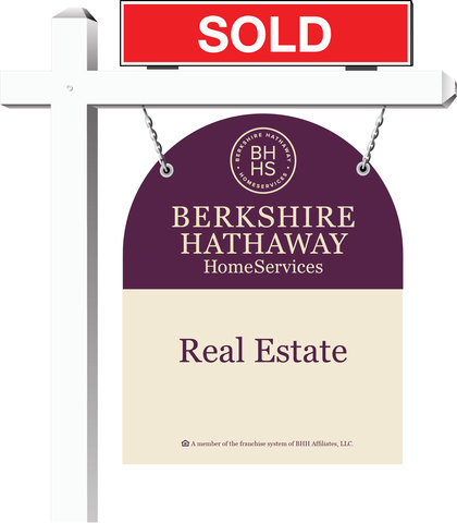 """Sold"" sign atop a real estate yard sign"