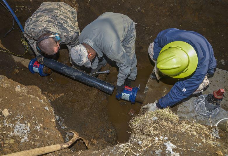 workers repairing a pipeline